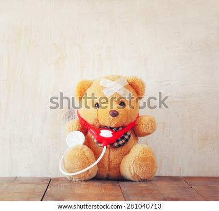Teddy Bear with Bandage  and  stethoscope over wooden background