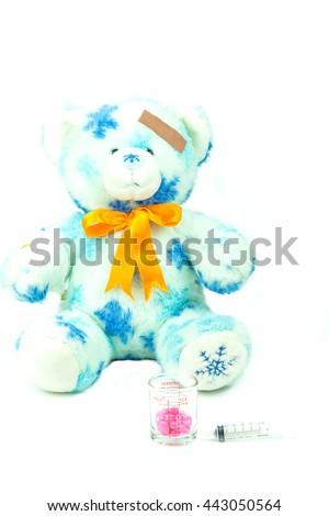 Teddy bear with bandage, drug and hypodermic syringe isolated on white background - stock photo