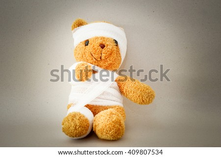 Teddy bear with bandage on gray background. - stock photo