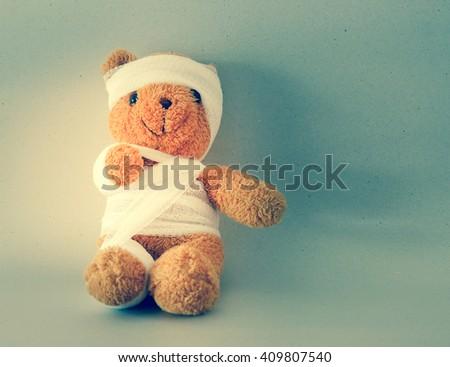 Teddy bear with bandage on vintage style. - stock photo