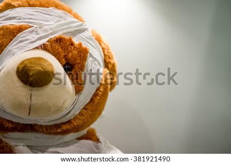 teddy bear with bandaged head on white background - stock photo