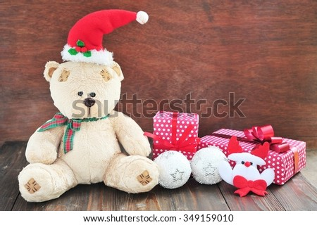 Teddy bear with Christmas presents  on wooden .