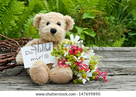 teddy bear with flowers and card with lettering miss you/miss you/teddy