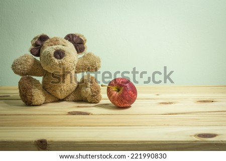 teddy bear with fruit on wooden table over grunge background - stock photo
