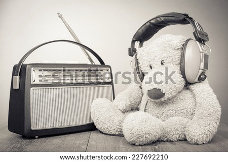 Teddy Bear with headphones and retro radio. Vintage old style sepia photo - stock photo