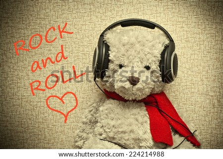 Teddy bear with headphones. Lover of music and rock and roll. Photo tinted in yellow - stock photo