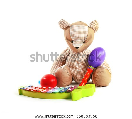 Teddy bear with maracas and xylophone, isolated on white - stock photo