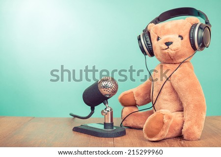 Teddy Bear with retro microphone and headphones front mint green background - stock photo