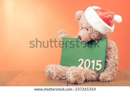 Teddy Bear with Santa hat and sign board for New Year 2015 greeting card background - stock photo