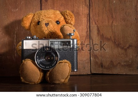 teddy bear with vintage camera on wood background - stock photo