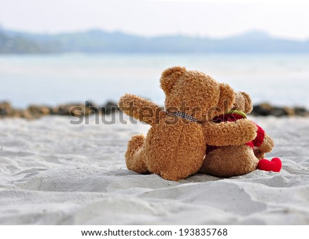 Teddy bears sitting on the beautiful beach with love. Concept about love and relationship - stock photo