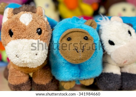 Teddy donkey, blue monkey and stuffed cow posing to camera. Friendship