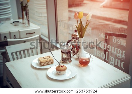 tee and cake in a nice cafe. Photos in purple tones - stock photo