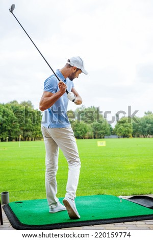 Teeing off. Full length rear view of young male golfer playing golf - stock photo