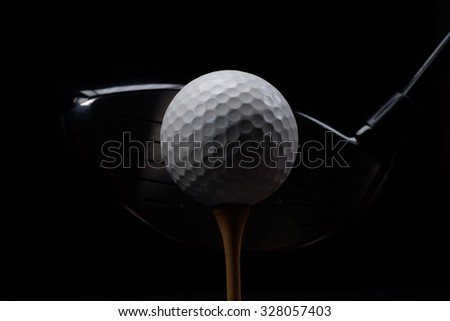Teeing off/Golf ball club and tee on black background