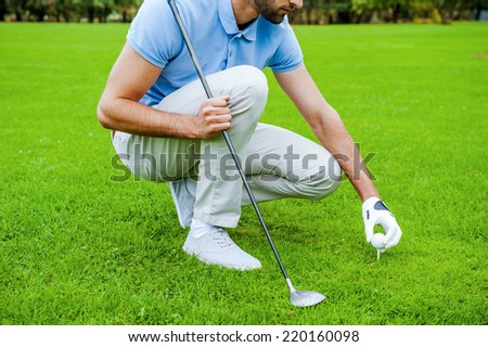 Teeing up. Close-up of golfer placing a golf ball on tee prior  - stock photo