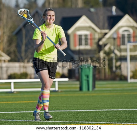 Teen age girls lacrosse player passing the ball as she runs down the field. - stock photo