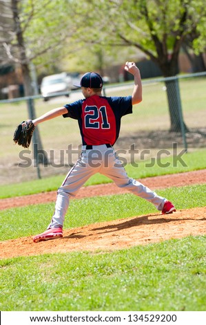 Teen baseball boy pitcher in the middle of a pitch. - stock photo