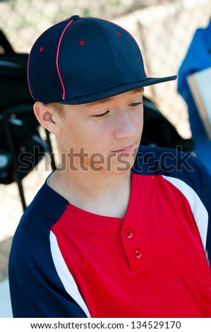 Teen baseball player looking sad in dugout. - stock photo