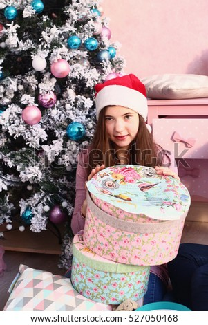 teen beautiful girl in pink woolen dress with christmas decoration and tree on shabby chick room background