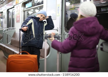 Teen boy and girl in a jacket with suitcases in an empty subway car - stock photo