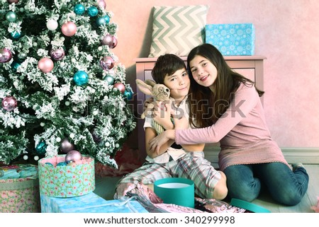 teen boy and girl siblings with presents toy and christmas tree background - stock photo