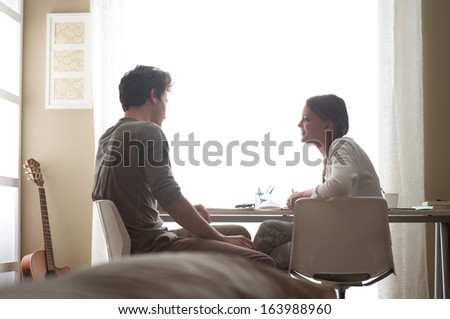 Teen boy and girl sitting together and studying at home