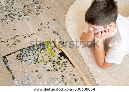 Teen boy collects a puzzle lying on the carpet