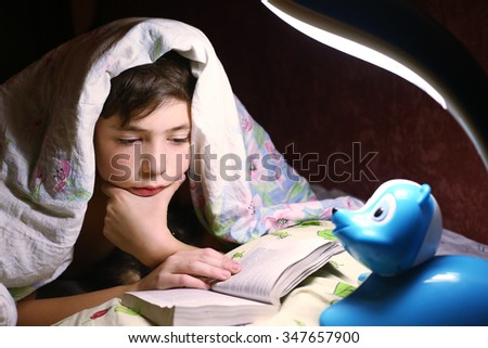 teen boy engaged in intriguing reading book under the blanket in night hour - stock photo