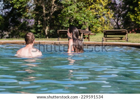Teen Boy Girl Swim Pool Hangout Teenagers girl boy swim pool hangout summers day home talk laugh playtime - stock photo