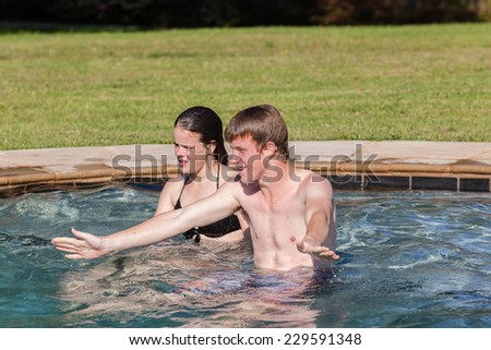Teen Boy Girl Swim Pool Playtime Teenagers girl boy swim pool hangout summers day home talk laugh playtime - stock photo