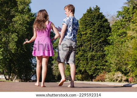 Teen Boy Girl Walking Hangout Teenagers girls boy hangout summers day home talk laugh playtime walking away. - stock photo