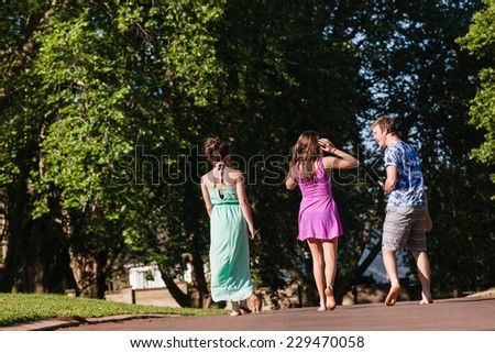 Teen Boy Girls Walking Talking  Teenagers girls boy hangout summers day home walking talk laugh playtime - stock photo
