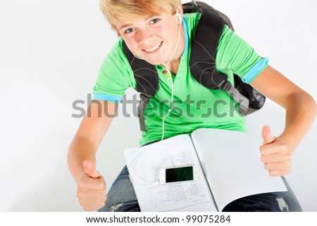 teen boy giving thumbs up while reading book - stock photo
