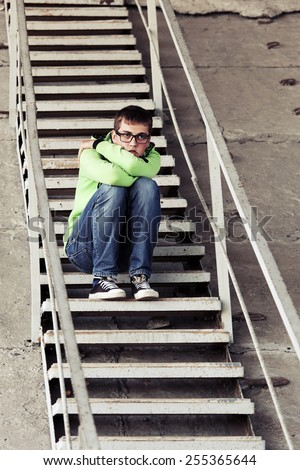 Teen boy in depression sitting on the steps  - stock photo