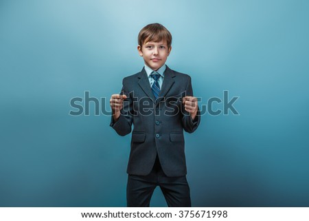 Teen boy of twelve European appearance in a business suit shows his fists on a blue background - stock photo