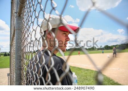 Teen boy on sidelines at baseball practice - stock photo