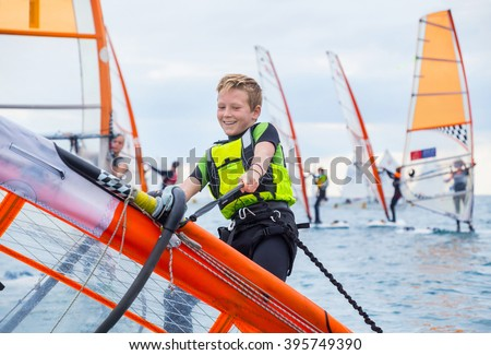 Teen boy raises windsurfing sail in the sea - stock photo