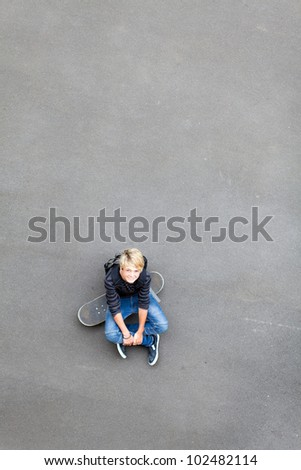 teen boy sitting on skateboard and looking up - stock photo