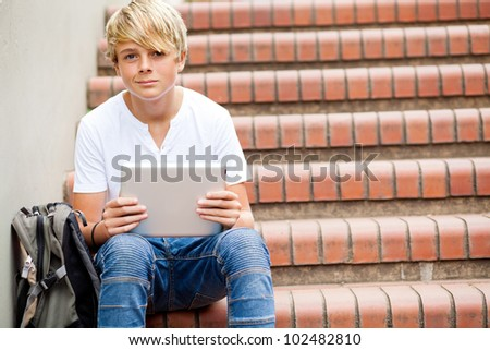 teen boy sitting on stairs and using tablet computer in school - stock photo