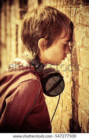 Teen boy standing in the street, turned away to face the wall. Sadness, depression. Teenage problems.