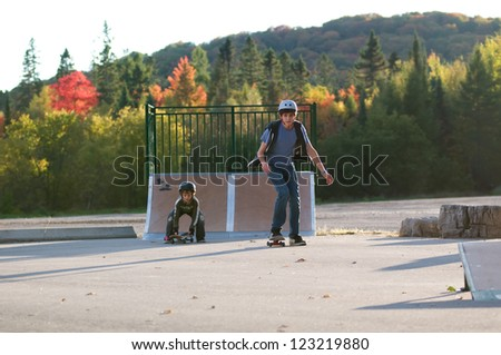 teen boy teaching younger brother to skateboard at the local outdoor skate park on a beautiful fall evening - stock photo