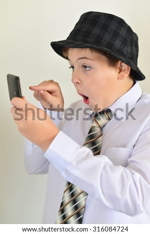 Teen boy with surprise looks at a mobile phone - stock photo