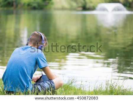Teen boy with tablet pc and headphones listening to music or watching video at lakeside. Child have rest near water in park.