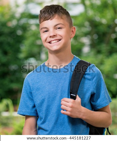 Teen boy 12-14 year old with schoolbag posing outdoors.