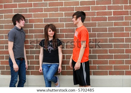 teen boys and girl outside school building