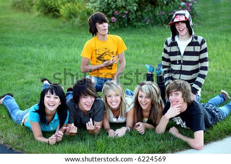 teen boys and girls outside having fun in grass - stock photo