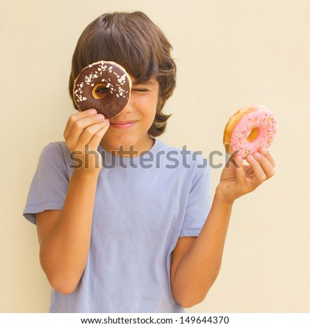 teen  caicasian boy playing with  donuts - stock photo