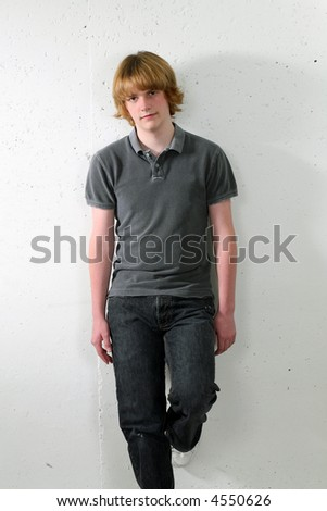 teen caucasian boy full length leaning on wall