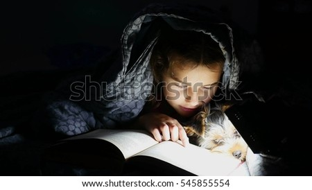 teen child reading girl reads a book dog at night with flashlight lying under a blanket